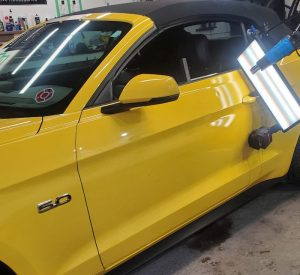 Door ding repaired on a ford mustang