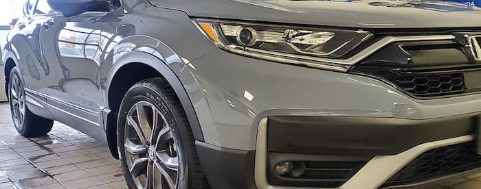 Grey SUV being serviced by Magic Dent Repair offer paintless dent repair in Toronto and the GTA area