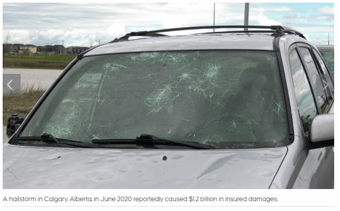 Car with severe dents and broken windshield from hail